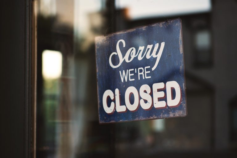 A sorry we're closed sign on a storefront